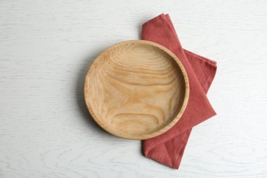 Empty plate and napkin on white wooden table, flat lay
