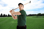 Mladý muž hraje golf na hřišti se zelenou trávou