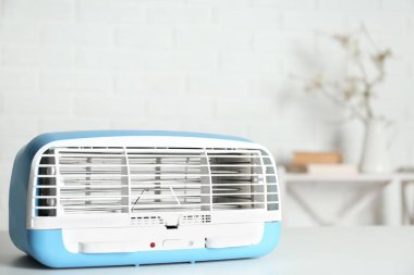 Modern air purifier on white table in room