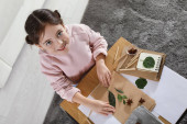 Little girl working with natural materials at table indoors, top view. Creative hobby
