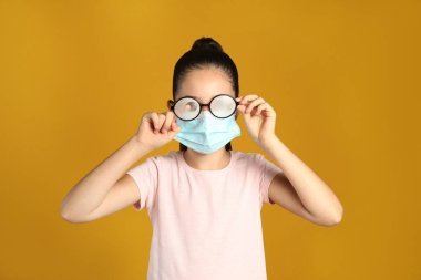 Little girl wiping foggy glasses caused by wearing medical face mask on yellow background. Protective measure during coronavirus pandemic