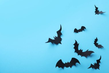 Paper bats on light blue background, flat lay with space for text. Halloween decor