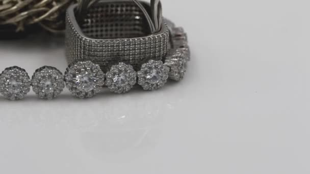 Elegant silver square diamond ring and bracelet with large gemstones rotate on the stand