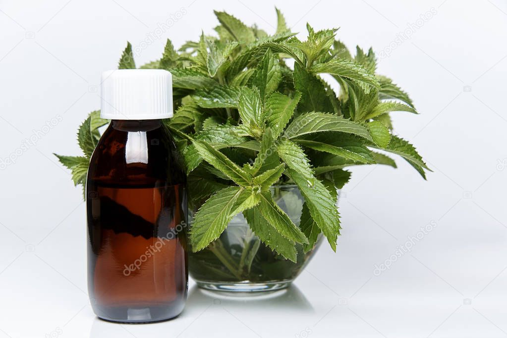 A bottle of medicine is next to a glass bowl with fresh sprigs of mint.