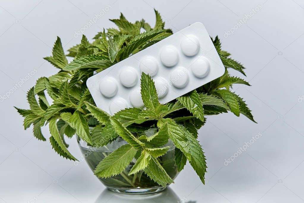 A plate of pills lies on the branches of mint in a glass bowl with water.