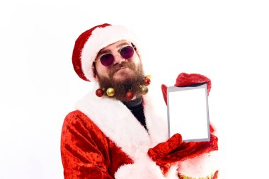 A young man in a Santa Claus costume with Christmas toys in his beard is holding a tablet with a blank white screen. Copy of space.