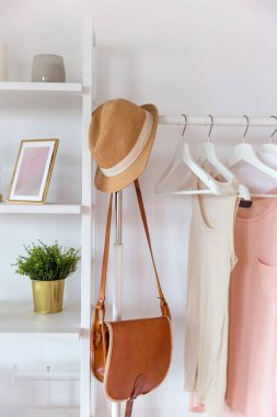 Organic cotton in trendy colors on a hanger and interior items on shelves in a cozy style