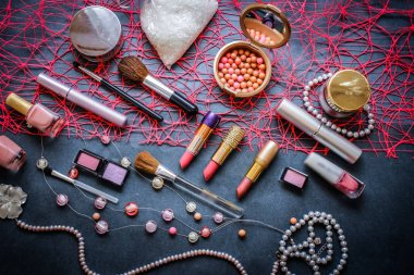 Women's cosmetics on a dark graphite background: pink lipstick of 3 shades, pink and peach eyeshadow, polka-dot powder, salt for baths, nail polish gently pink, mascara, a string of pink pearls