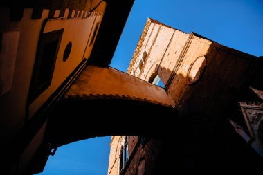 low angle view of beautiful ancient arch and tower against blue sky, florence, italy
