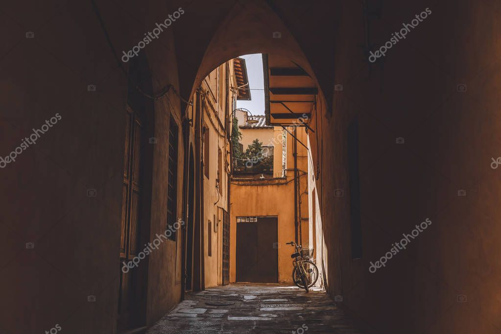 arch in ancient buildings with bicycle, Pisa, Italy