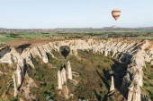 Photo single hot air balloon flying above beautiful famous rock formations in cappadocia, turkey