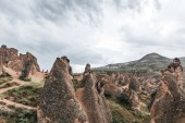 Photo majestic geological formations and cloudy sky in cappadocia, turkey