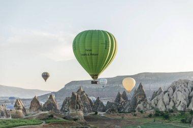 CAPPADOCIA, TURKEY - 09 MAY, 2018: hot air balloons flying above beautiful rock formations in goreme national park, cappadocia, turkey stock vector