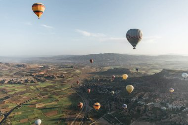 CAPPADOCIA, TURKEY - 09 MAY, 2018: colorful hot air balloons flying above majestic landscape in cappadocia, turkey stock vector