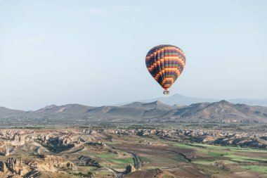 colorful hot air balloon flying above goreme national park, cappadocia, turkey
