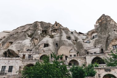 low angle view of beautiful rock formations and buildings in cappadocia, turkey