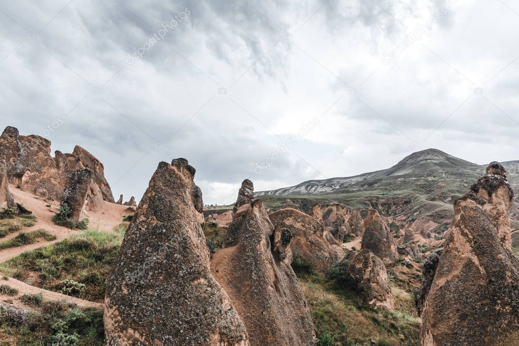 majestic geological formations and cloudy sky in cappadocia, turkey