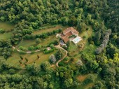 Fotografie aerial view of villa with swimming pool between forest in Italy