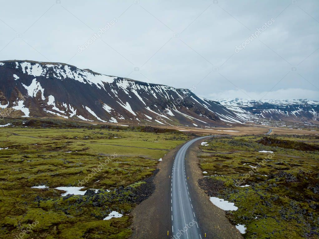aerial view of road between fields and mountains with snow, snaefellsnes, iceland