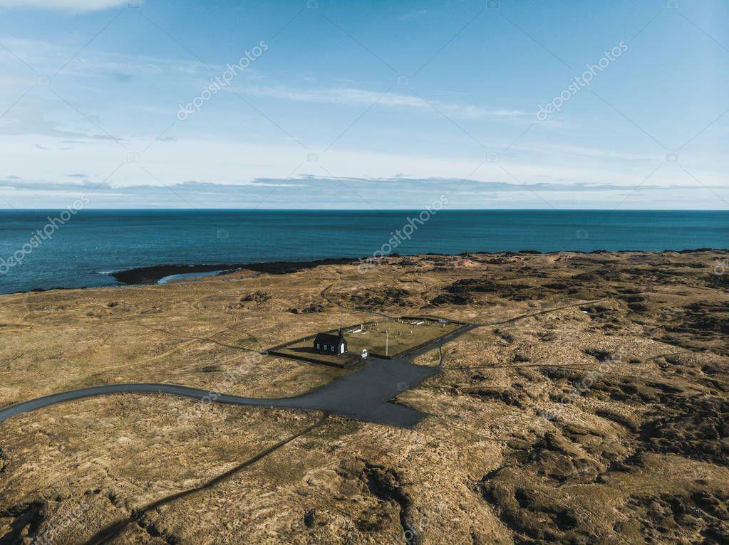 aerial view of small black Budir Church near beautiful sea, snaefellsnes, iceland