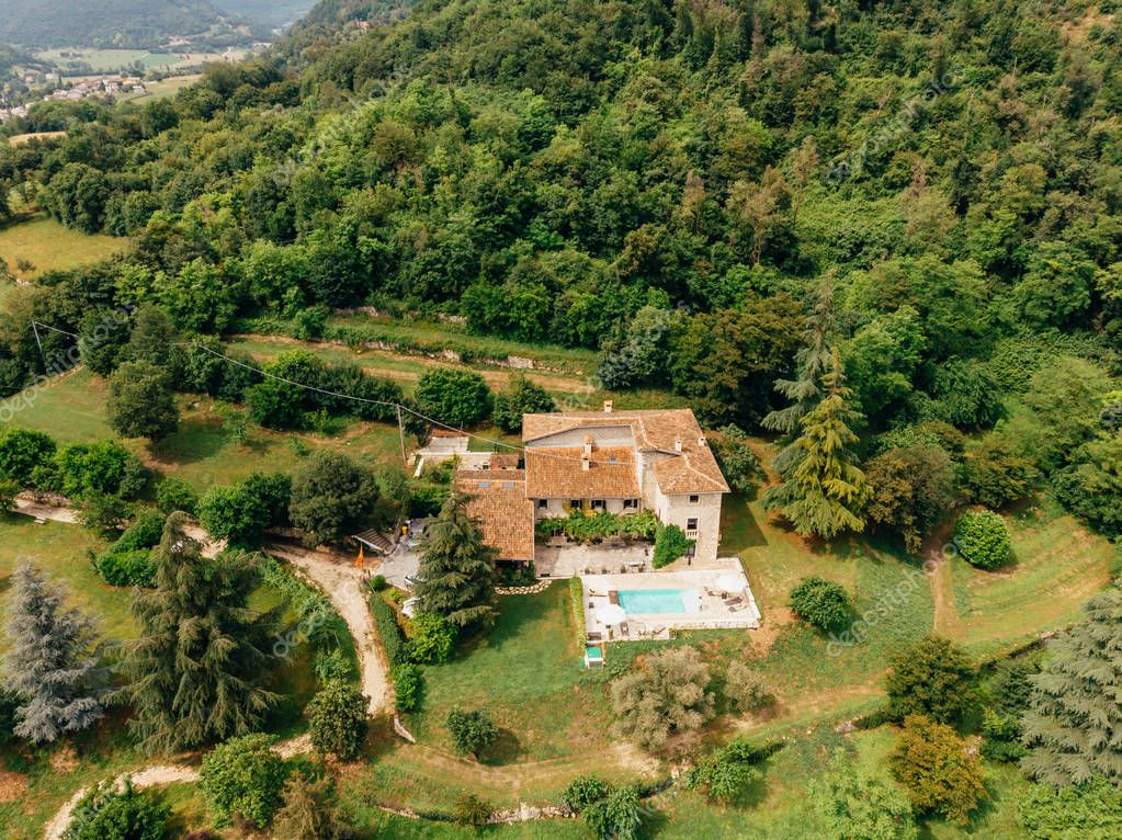 aerial view of couple resting at swimming pool near villa in Italy