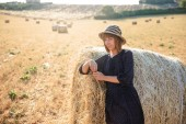 krásná mladá žena se v balíku sena a při pohledu na fotoaparát, provence, Francie