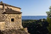 Fotografie staré kamenné budovy a střechy, zeleň a vzdálené hory v provence, Francie