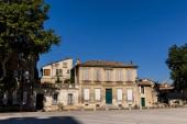 Fotografia Via vuota con vecchie case tradizionali e gli alberi verdi al giorno pieno di sole, Provenza, Francia