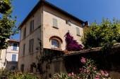 nízký úhel pohled na krásné tradiční dům se zelenou vegetací a kvetoucí květiny na slunečný den, provence, Francie