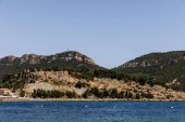 Fotografie beautiful rocky mountains with green vegetation and tranquil seascape in provence, france