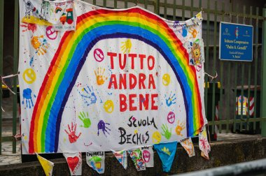 Turin, Piedmont, Italy. May 2020. Coronavirus pandemic. On the facades of the houses hang the sheets with the drawing of the rainbow and message everything will be fine. stock vector
