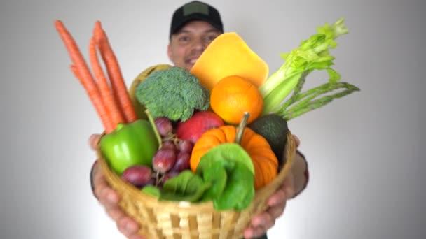 Kosár friss bio gyümölcsök és zöldségek a kezében mosolygó farmer