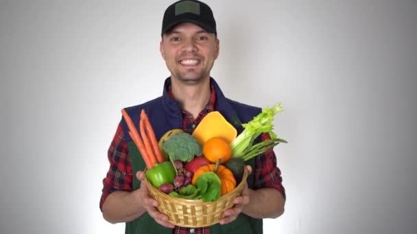 Mosolygó farmer Man Holding kosár friss szerves természetes gyümölcsök és zöldségek
