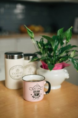 Cup of hot coffee and flower pot on wooden kitchen table