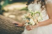 ženich je zůstat drží svatební květiny ve svatebních šatech