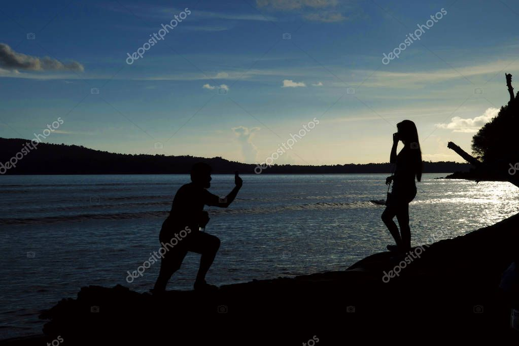 Silhouette of a man clicking photo of a woman against the setting sun, Chidiya Tapu at Andaman
