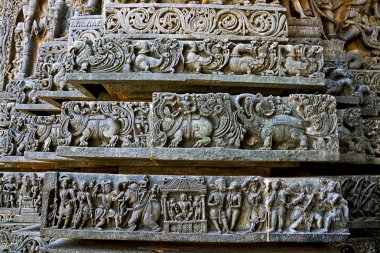 Friezes of animals, scenes from mythological episodes from Ramayana and Mahabharata, at the base of temple, Hoysaleshwara temple, Halebidu, Karnataka, India.