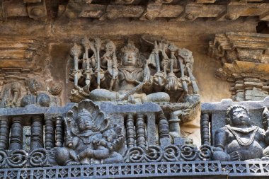 Ornate wall panel reliefs depicting Lord Vishnu as Narayana, the Supreme God, Chennakesava temple, Belur, Karnataka, india. Sixteen-armed Narayana is seated on a lotus that is upheld by a four-armed Garuda.