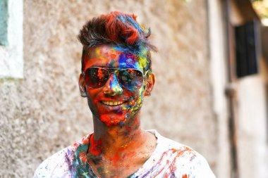 Young man celebrating of Holi festival with colored powder on face, Yerawada Pune, Maharashtra, India stock vector