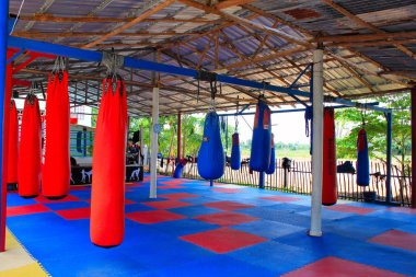 Muay Thai gym with boxing bags and colorful rubber floor at Ban Bung Sam Phan Nok, Phetchabun, Thailand