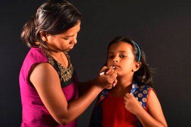 Woman make-up artist does makeup to a little girl, Pune, Maharashtra.