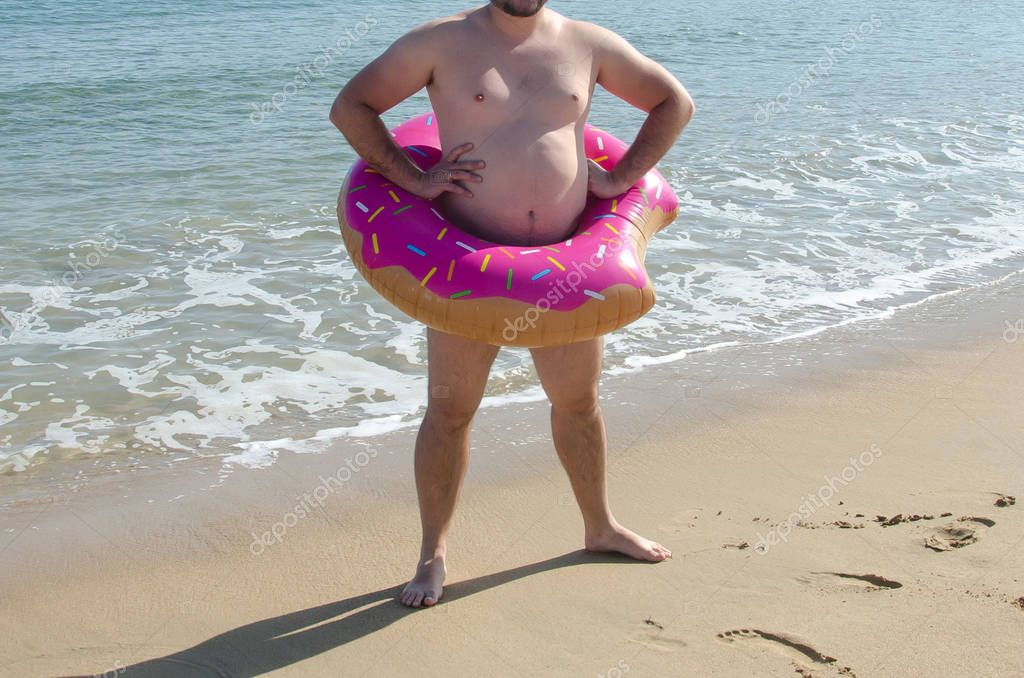 Obese man wearing inflatable donut ring on his belly on beach. C