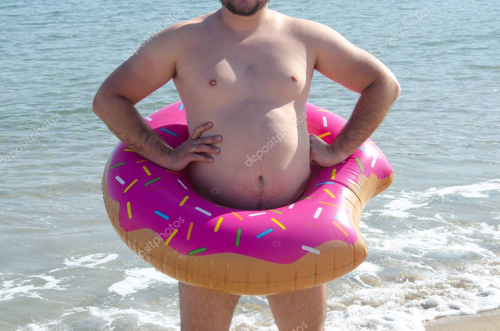 Fat man with obesity wearing inflatable donut ring on his belly