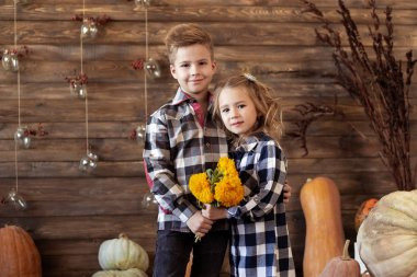 Boy and girl are standing in autumn background with pumpkins