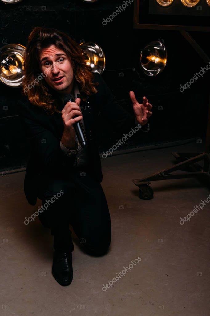 Brutal singer with microphone on the stage, with long hair, against the background of bright lanterns, scene