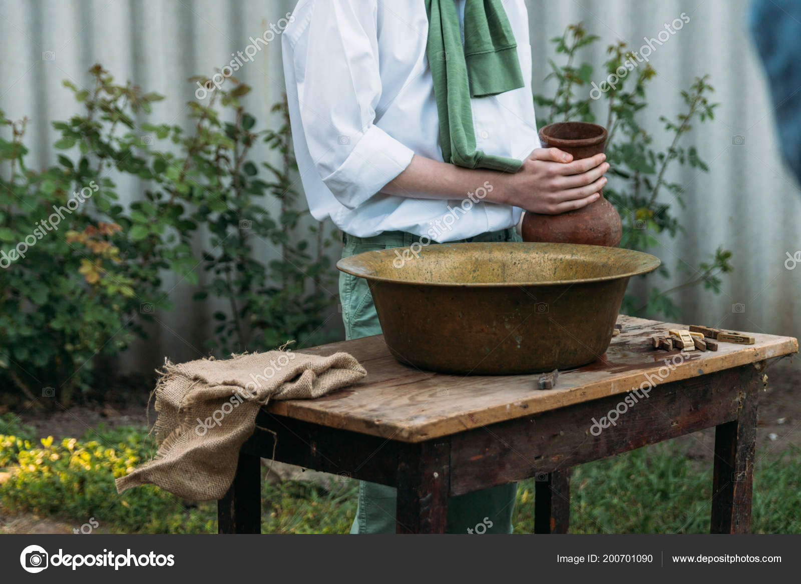 Boy White Shirt Green Sweater Holds Clay Jug Pours Water
