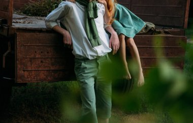 spying, to look from behind bushes. blurred leaves at the beginning of the snapshot. a barefooted girl in a green, vintage dress, the dress sits on the back of a red, old car and hugs the barefoot neck, next to a standing guy who is dressed in a whit