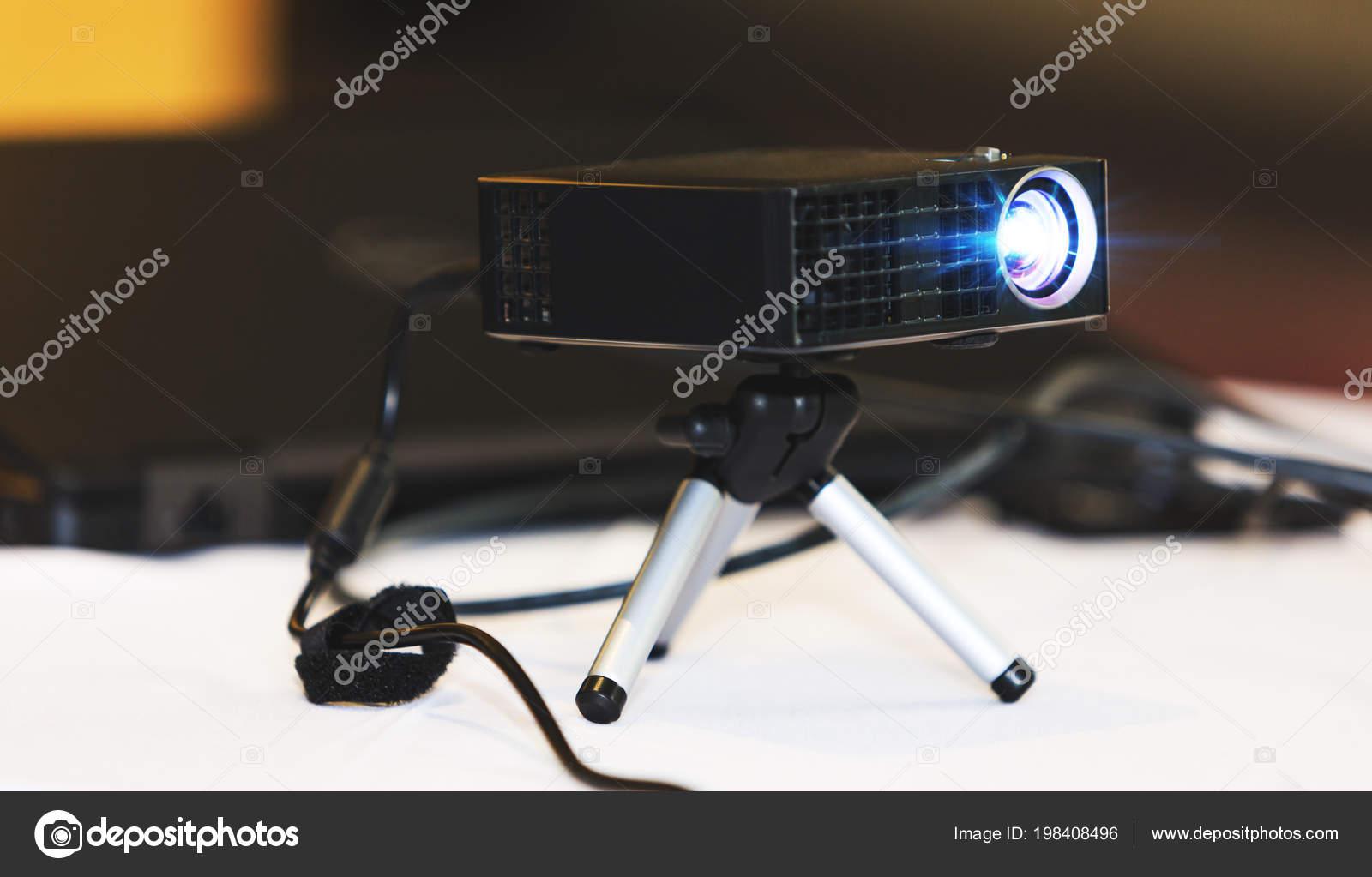 Projecteur noir avec trépied installé sur une table blanche en