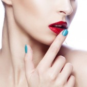 Oříznutý portrét ženy s červenými rty a modrý lak na nehty