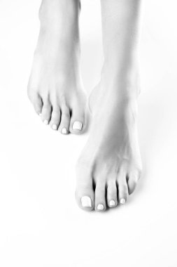 Close view of female feet with white manicure on white background